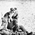 Eine Frau sitzt mit ihrem Hund auf einem Felsen an einem See.MR=YES